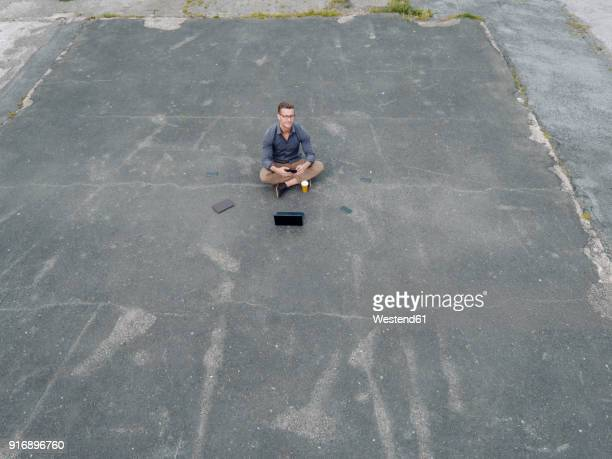Young businessman with coffee to go and several mobile devices sitting on tarmac