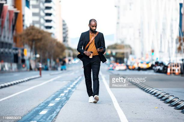 young businessman with coffee to go looking at cell phone while walking on the street - black jacket stock pictures, royalty-free photos & images