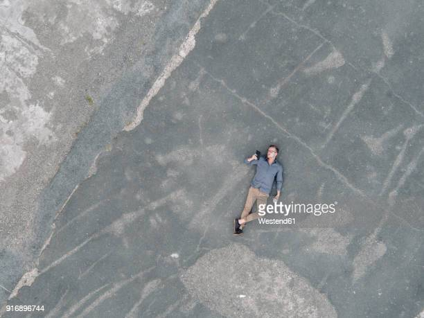 young businessman with coffee to go lying on tarmac using mini tablet, quadcopter view - schrägansicht stock-fotos und bilder