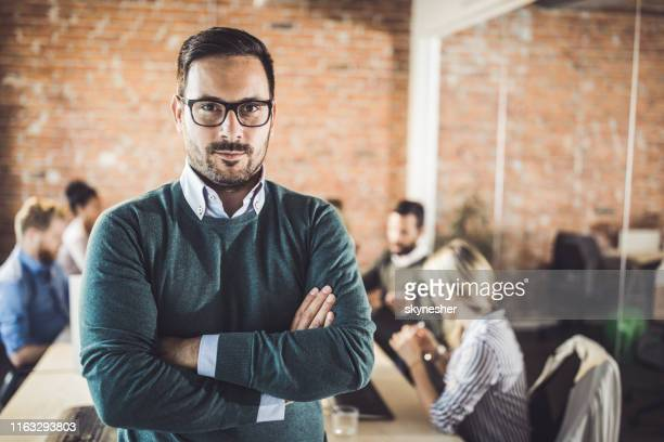 Young businessman with crossed arms at corporate office.