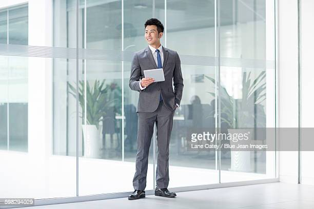 young businessman with digital tablet - businesswear stock pictures, royalty-free photos & images