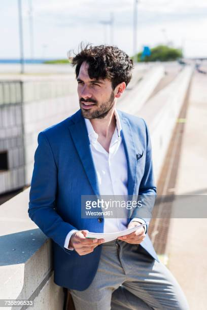 Young businessman with documents outdoors