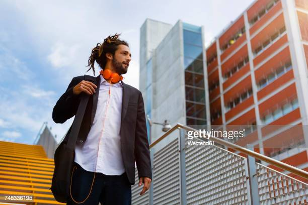 Young businessman with dreadlocks walking downstairs