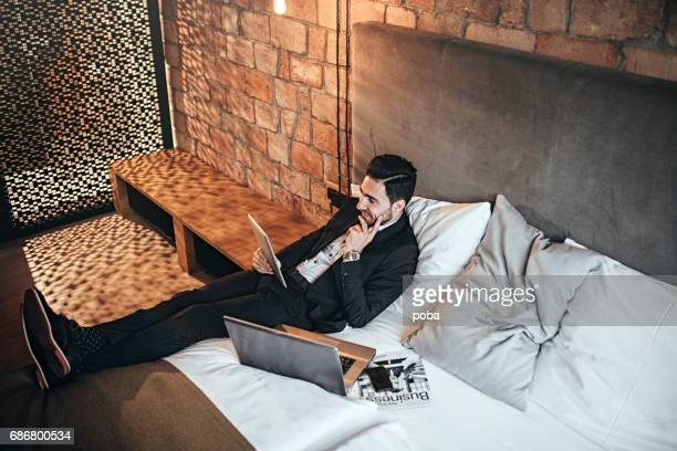 Junge Geschäftsmann mit elektronischen Geräte im Hotel