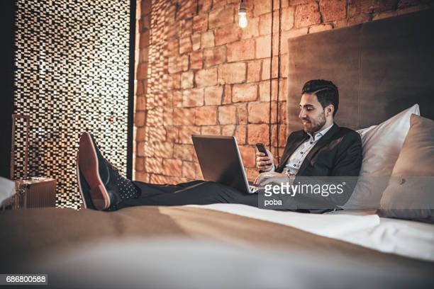 Young businessman with electronic devices in hotel