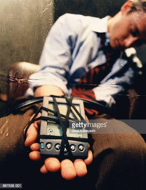 young businessman with electronic organizer tied to hand (distressed) - man tied to chair stock photos and pictures