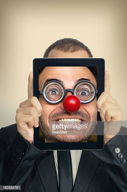 young businessman with funny face in a digital tablet - happy clown faces stock photos and pictures