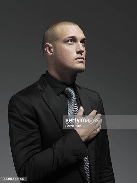 Young businessman with hand on heart