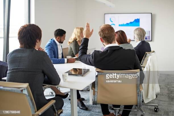 ビデオ会議中に手を挙げた若いビジネスマン - 大型テレビ ストックフォトと画像