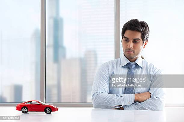Young businessman with hands folded looking at car model