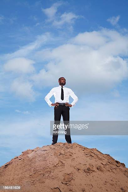 Young businessman with hands on hips in the desert