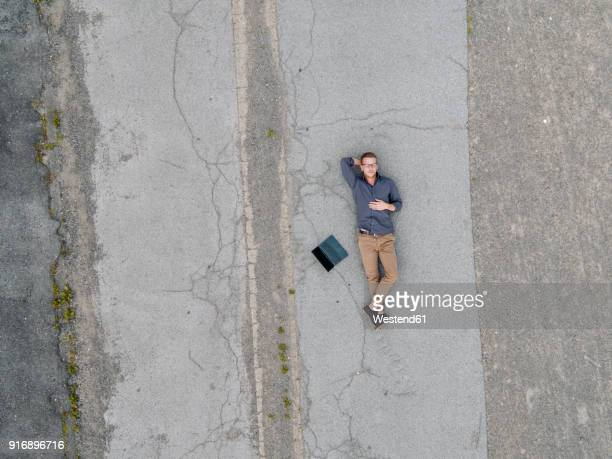 young businessman with laptop relaxing in solitude, quadcopter view - lying down ストックフォトと画像