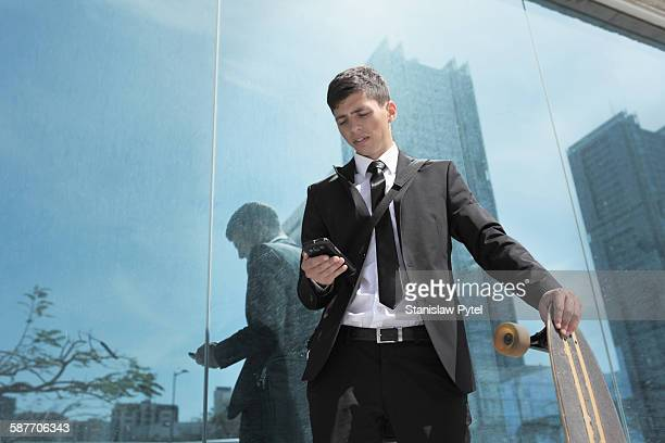 Young businessman with longboard checking phone