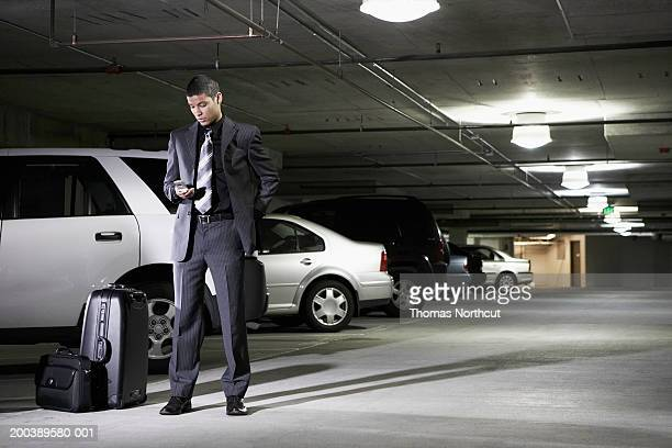 Young businessman with luggage using cell phone in parking garage