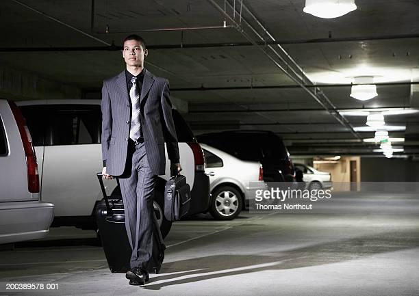 Young businessman with luggage walking through parking garage