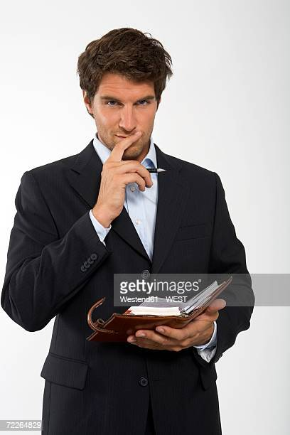 Young businessman with personal organizer, close-up, portrait