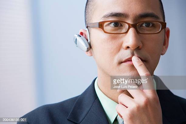 Young businessman with phone ear piece, close-up