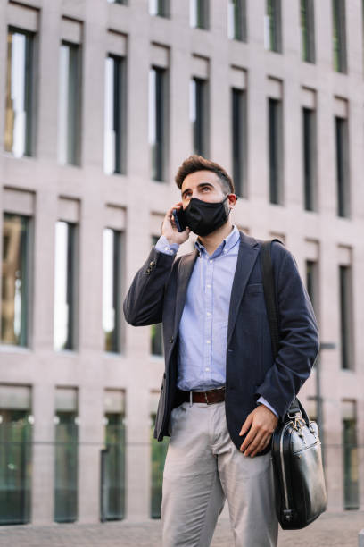 Young businessman with protective face mask having mobile phone conversation outdoors in a modern corporate district