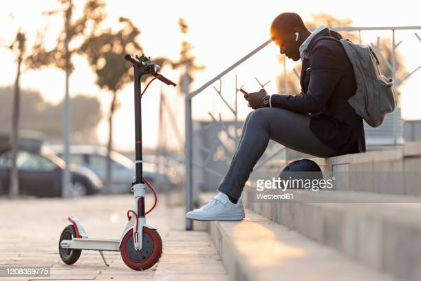 young businessman with push scooter sitting on stairs at sunset using mobile phone and earphones - electric scooter stock pictures, royalty-free photos & images