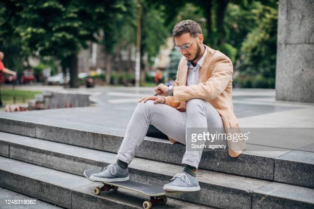 jeune homme d'affaires avec la planche à roulettes s'asseyant sur des étapes et vérifiant l'heure - décontracté chic photos et images de collection