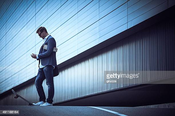 Young businessman with skateboard using smartphone in the urban