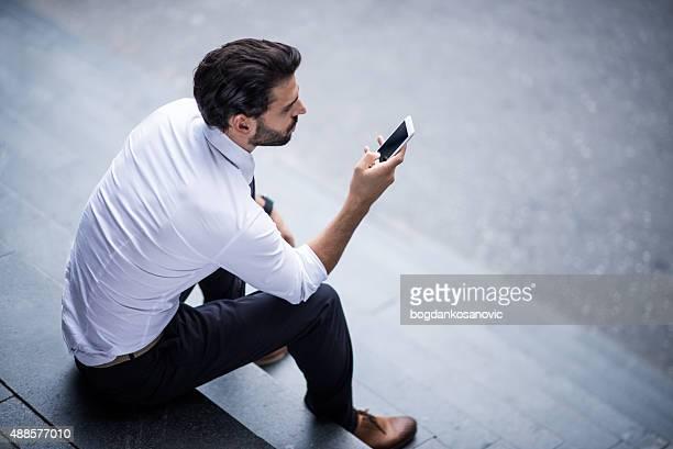Junger Geschäftsmann mit Smartphone sitzen auf der Treppe