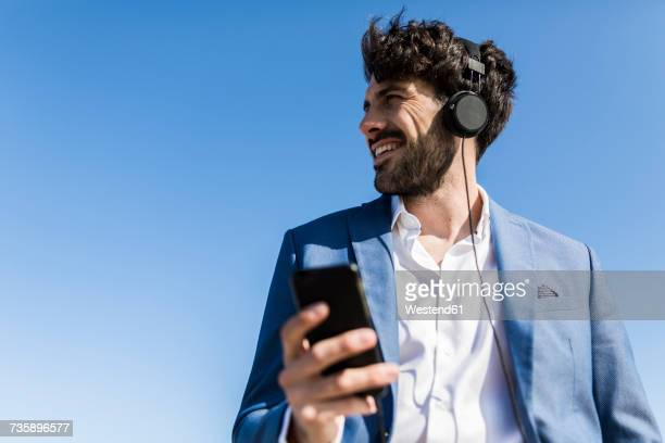 young businessman with smartphone wearing headphones under blue sky - vista de ángulo bajo fotografías e imágenes de stock