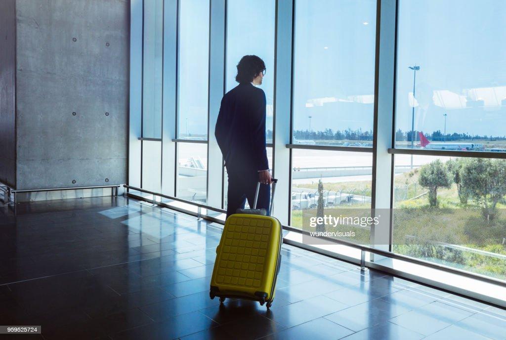 Junger Geschäftsmann mit Koffer Blick durch Fenster am Flughafen : Stock-Foto