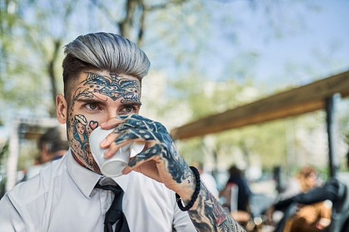 Young businessman with tattooed face, drinking coffee - gettyimageskorea