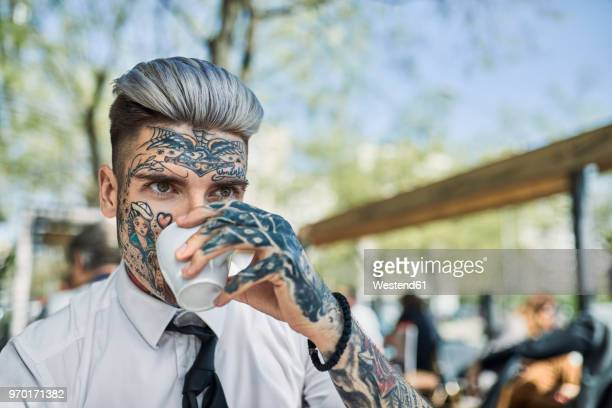 Young businessman with tattooed face, drinking coffee