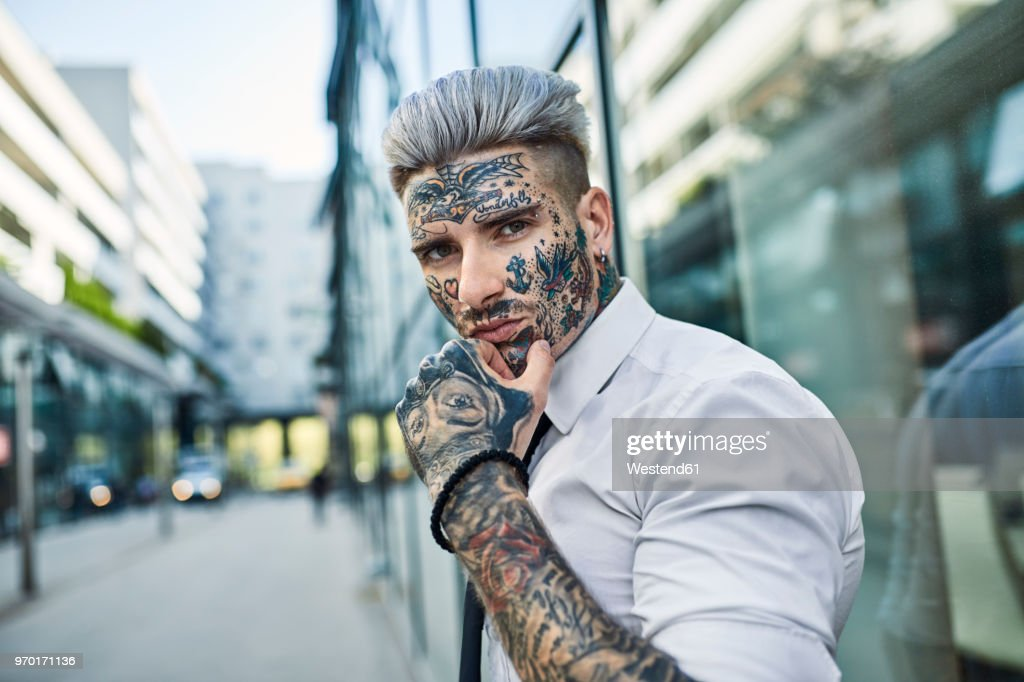 Young businessman with tattooed face walking in the city, portrait : Stock-Foto