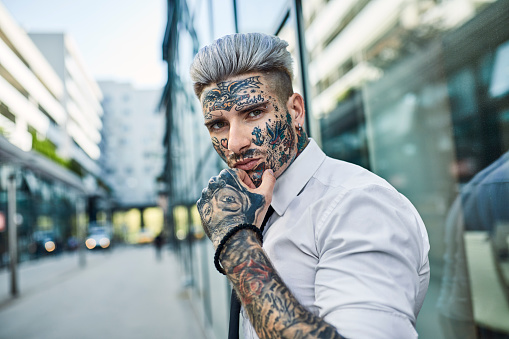 Young businessman with tattooed face walking in the city, portrait - gettyimageskorea