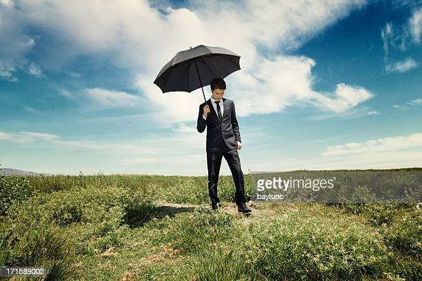 Young businessman with umbrella