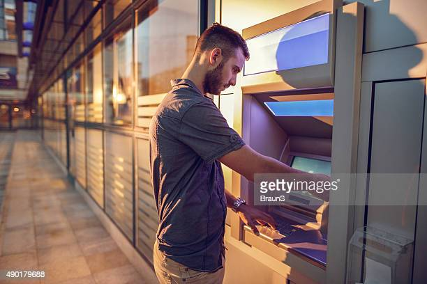 Young businessman withdrawing money from a cash machine.