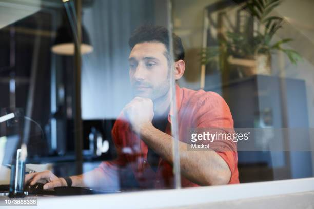 Young businessman working at computer desk seen through glass in office