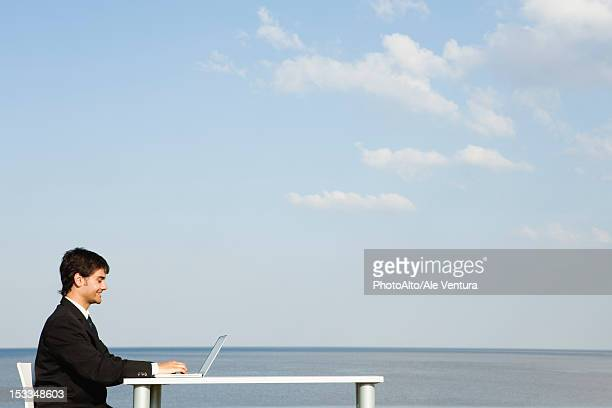 Young businessman working at desk by ocean, side view