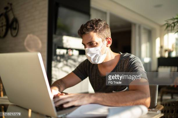 young businessman working at home with face mask - n95 respirator mask stock pictures, royalty-free photos & images