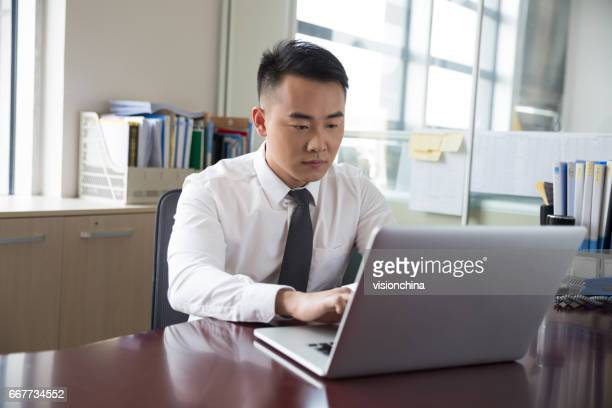 young businessman working at laptop in office