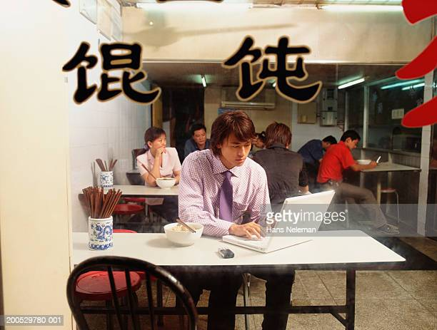 Young businessman working at laptop in restaurant