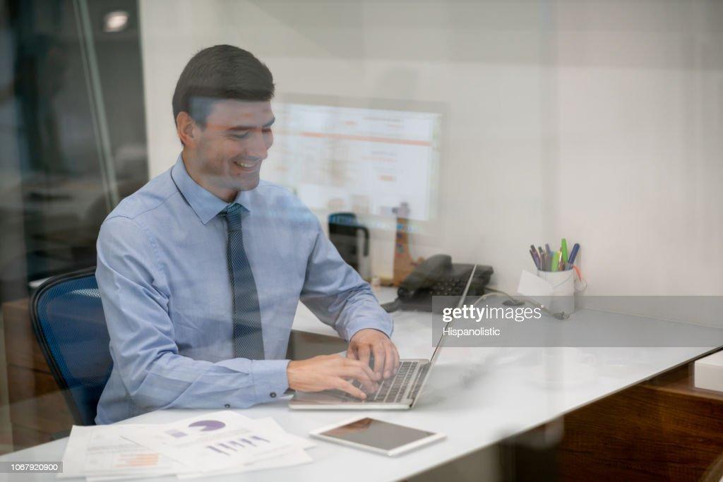 Jovem empresário, trabalhando no escritório no laptop olhando muito feliz : Foto de stock
