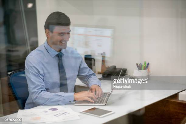 Young businessman working at the office on laptop looking very happy