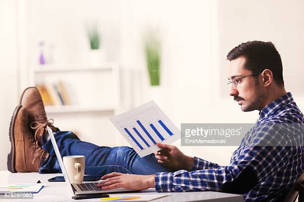 Young businessman working from home analyzing data using laptop.