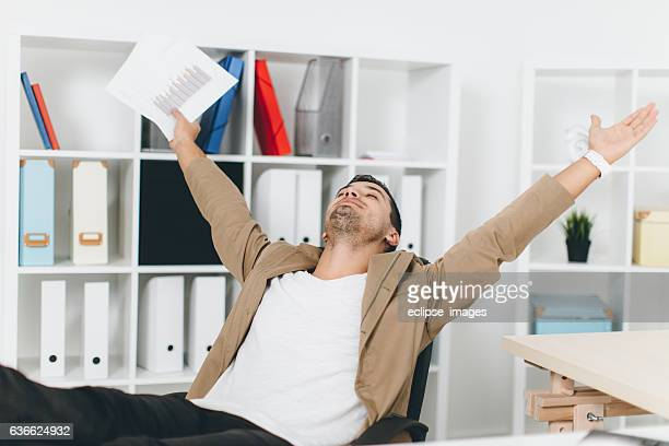 Young businessman working from home analyzing data using laptop