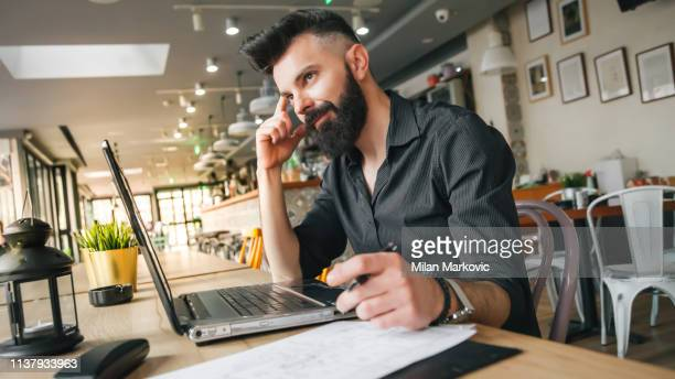 young businessman working in cafe - internet cafe stock pictures, royalty-free photos & images