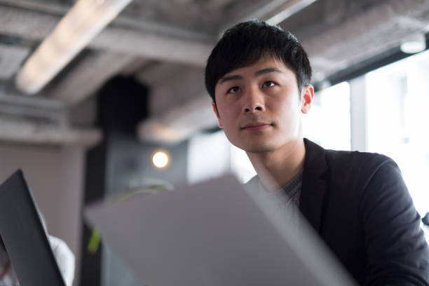 young businessman working in co-working space - asain office man stock pictures, royalty-free photos & images