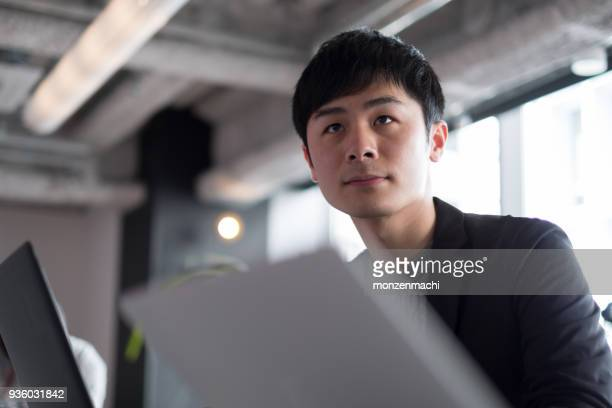 young businessman working in co-working space - japanese ethnicity stock pictures, royalty-free photos & images