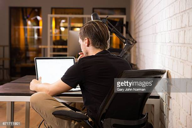 Young businessman working in office at night.