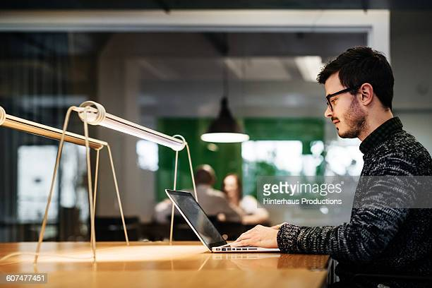 young businessman working late in his office. - incidental people stock pictures, royalty-free photos & images