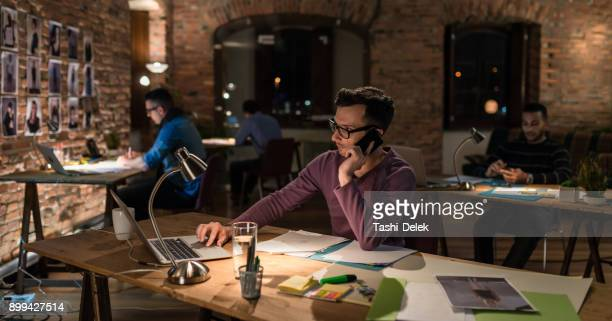 young businessman working late - design studio stock pictures, royalty-free photos & images