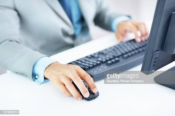 Young businessman working on computer with hand in focus